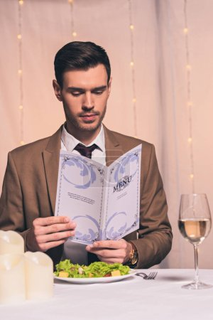 Photo for Handsome, elegant man reading menu while sitting at restaurant - Royalty Free Image