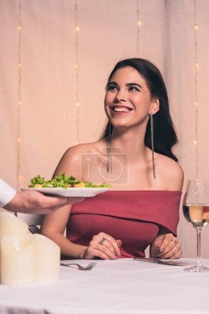 Photo for Cropped view of waiter holding plate with fresh salad near cheerful, elegant girl - Royalty Free Image