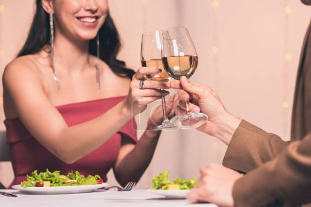 cropped view of woman clinking glasses of white wine with boyfriend while sitting in restaurant