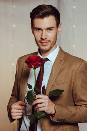 Photo pour Bel homme élégant tenant rose rouge tandis que debout dans le restaurant et regardant la caméra - image libre de droit