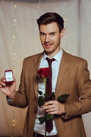 Photo pour Élégant, bel homme tenant boîte avec bague de mariage et rose rouge tout en souriant à la caméra dans le restaurant - image libre de droit