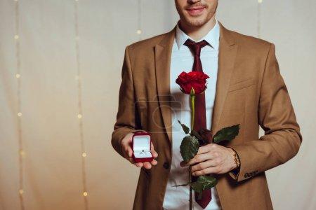 Photo pour Vue partielle de l'homme élégant tenant boîte avec bague de mariage et rose rouge tout en se tenant dans le restaurant - image libre de droit