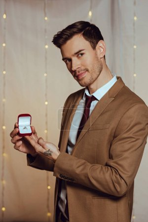 Photo for Elegant, handsome man holding box with wedding ring while looking at camera - Royalty Free Image