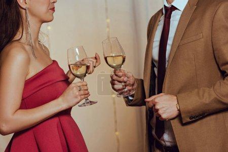 Photo pour Vue recadrée de l'homme et de la femme élégants tenant des verres de vin blanc au restaurant - image libre de droit