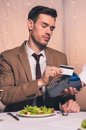 Photo for Partial view of waiter with payment terminal near handsome man holding credit card while sitting in restaurant - Royalty Free Image