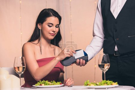 Photo for Cropped view of waiter holding payment terminal near beautiful, elegant girl sitting at served table - Royalty Free Image