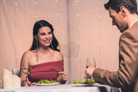 happy, elegant girl and handsome boyfriend sitting at served table in restaurant and holding glasses of white wine