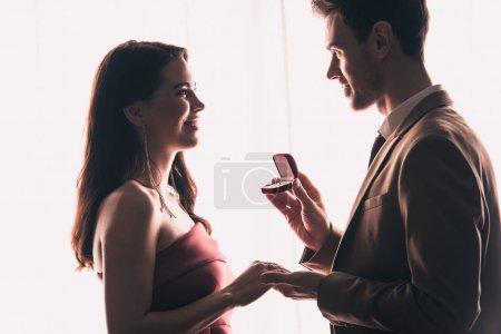 Photo pour Vue de côté de bel homme tenant la main de petite amie heureuse tout en faisant la demande en mariage sur les valentines - image libre de droit