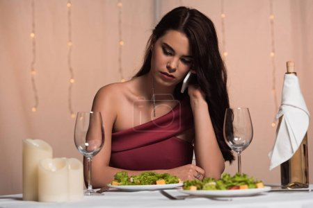 Photo for Disappointed, elegant girl sitting at served table in restaurant and talking on smartphone - Royalty Free Image