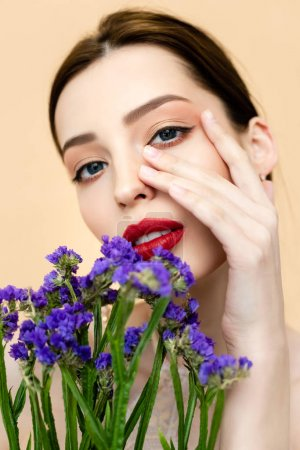 beautiful woman looking at camera and touching face near purple flowers isolated on beige
