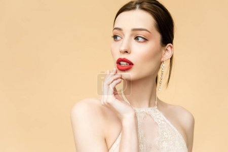 attractive young woman touching face isolated on beige