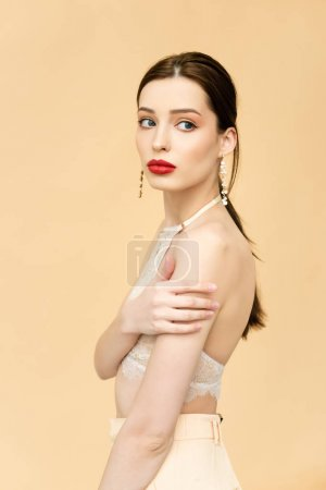 attractive young woman looking away and standing isolated on beige