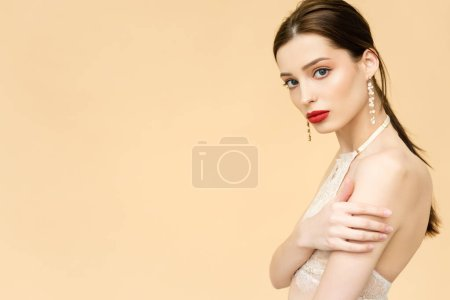 Photo for Attractive young woman looking at camera isolated on beige with copy space - Royalty Free Image