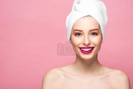 glückliche nackte Frau in weißem Handtuch schaut in die Kamera isoliert auf rosa
