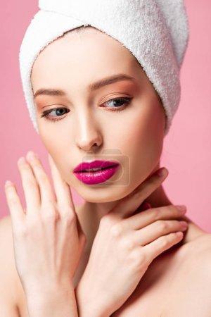 Photo pour Belle jeune femme en serviette blanche touchant le cou isolé sur rose - image libre de droit