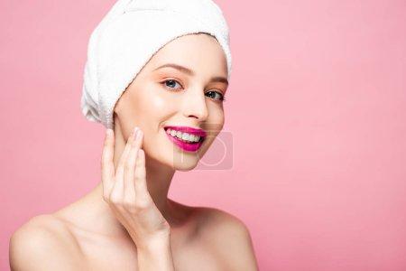 Photo pour Sourire femme nue en serviette blanche toucher visage isolé sur rose - image libre de droit