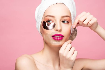 Photo for Naked young woman in towel applying eye patches isolated on pink - Royalty Free Image
