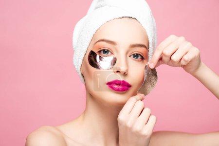 Photo pour Belle jeune femme en serviette appliquant des taches oculaires isolées sur rose - image libre de droit