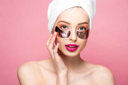 Photo for Beautiful young woman in towel and eye patches isolated on pink - Royalty Free Image
