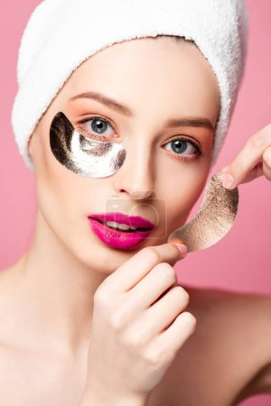 Photo for Beautiful woman in while towel applying eye patches isolated on pink - Royalty Free Image