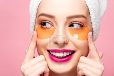Photo pour Une fille souriante touchant le visage avec des taches aux yeux et regardant loin isolée sur rose - image libre de droit