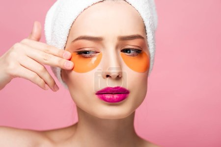 Photo pour Pretty girl touching face with eye patches isolated on pink - image libre de droit