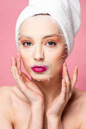 Photo for Young naked woman in moisturizing face mask touching face isolated on pink - Royalty Free Image