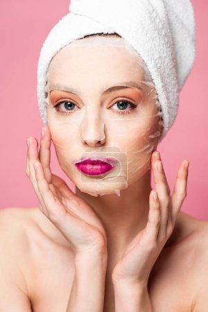 Photo pour Jeune femme nue dans hydratant visage masque toucher visage isolé sur rose - image libre de droit