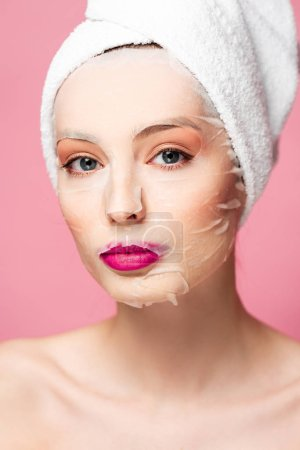 Photo pour Young naked woman in moisturizing face mask looking at camera isolated on pink - image libre de droit