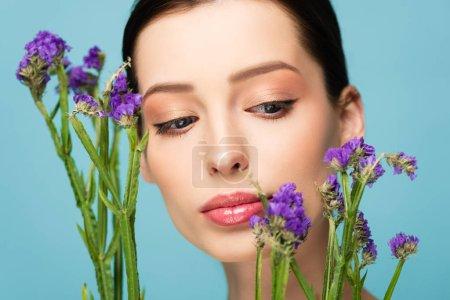 Photo pour Beautiful woman looking at limonium flowers isolated on blue - image libre de droit