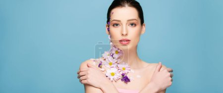Photo for Panoramic shot of attractive woman with flowers and crossed arms isolated on blue - Royalty Free Image