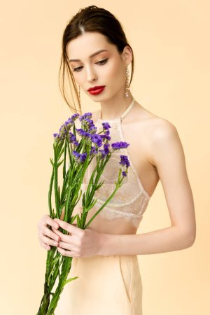 attractive woman looking at purple limonium flowers isolated on beige