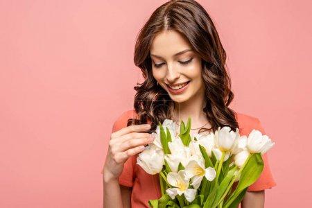 glückliches Mädchen lächelt, während sie einen Strauß weißer Tulpen berührt, isoliert auf rosa