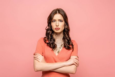 Photo for Displeased young woman standing with crossed arms while looking at camera isolated on pink - Royalty Free Image
