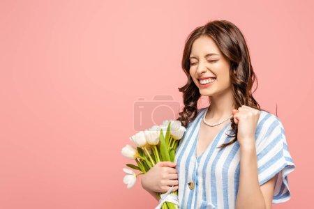 Photo pour Excité fille montrant oui geste tout en tenant bouquet de tulipes blanches isolées sur rose - image libre de droit