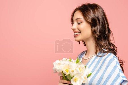 Photo pour Heureuse fille souriant avec les yeux fermés tout en tenant bouquet de tulipes blanches isolées sur rose - image libre de droit