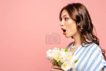 Photo pour Vue latérale d'une fille choquée tenant un bouquet de tulipes blanches debout avec la bouche ouverte isolée sur rose - image libre de droit