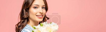 Photo pour Plan panoramique de fille heureuse tenant bouquet de tulipes blanches et regardant la caméra isolée sur rose - image libre de droit