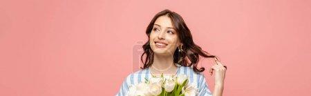 Photo pour Plan panoramique de gaie fille touchant les cheveux tout en tenant bouquet de tulipes blanches isolées sur rose - image libre de droit