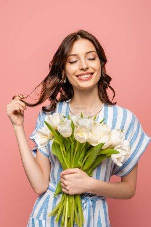 fröhliches Mädchen, das das Haar berührt, während es einen Strauß weißer Tulpen mit geschlossenen Augen hält, isoliert auf rosa