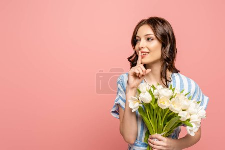 Photo for Attractive girl showing hush gesture while holding bouquet of white tulips isolated on pink - Royalty Free Image