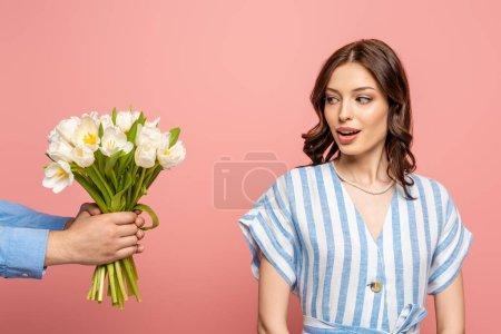 Photo pour Vue recadrée de l'homme présentant bouquet de tulipes blanches à la fille surprise isolé sur rose - image libre de droit