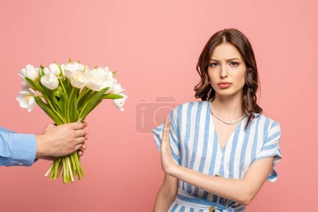Photo for Partial view of man presenting bouquet of white tulips to displeased girl showing no gesture isolated on pink - Royalty Free Image