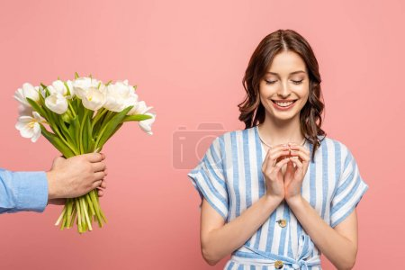 Photo for Partial view of man presenting bouquet of white tulips to happy girl standing with closed eyes isolated on pink - Royalty Free Image