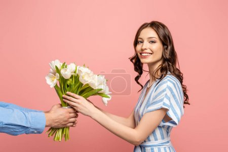 Photo for Cropped view of man presenting bouquet of white tulips to cheerful young woman isolated on pink - Royalty Free Image