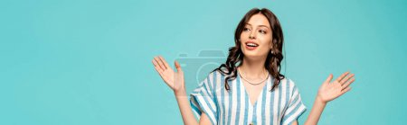 Photo for Panoramic shot of happy young woman looking away while standing with open arms isolated on blue - Royalty Free Image