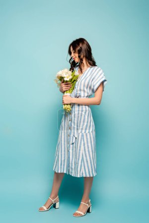Photo for Full length view of attractive young woman holding bouquet of white tulips on blue background - Royalty Free Image
