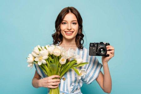 Photo pour Joyeuse jeune femme tenant un appareil photo numérique et un bouquet de tulipes blanches isolées en bleu - image libre de droit