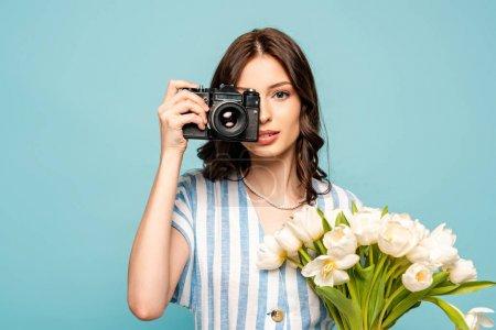 Photo pour Attrayant jeune femme prenant des photos sur appareil photo numérique tout en tenant bouquet de tulipes blanches isolées sur bleu - image libre de droit