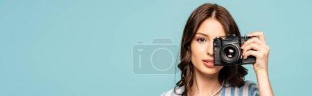 panoramic shot of attractive young woman taking picture on digital camera isolated on blue
